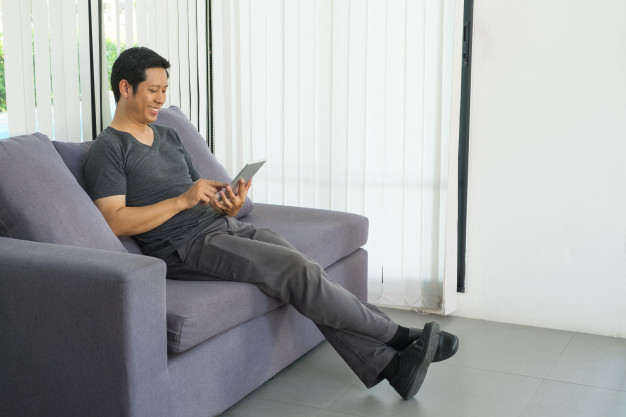 happy-relax-man-using-mobile-phone-sitting-comfortable-sofa_7189-1276